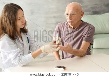 Doctor measuring blood sugar level of diabetic patient at home