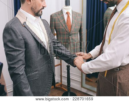 Tailor with client in atelier. Sewing custom made suit poster