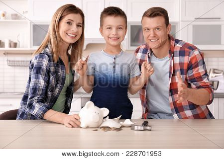 Happy family with broken piggy bank at home