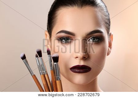 Beautiful woman and makeup brushes on light background. Professional visage artist work