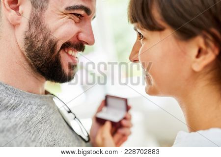 Young loving couple is looking at the purchase of wedding rings at the jeweler