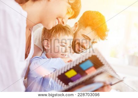 Family looks at photo album or picture book with son at home