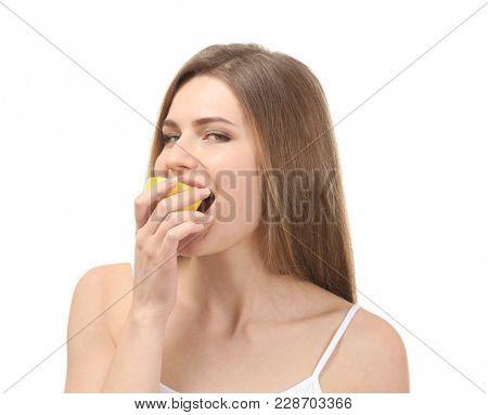 Beautiful young woman eating ripe lemon on white background