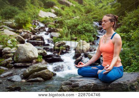Woman meditate in Hatha yoga asana Padmasana lotus pose outdoors at tropical waterfall