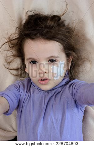 Little Girl With Adhesive Plaster On Face Making Selfie