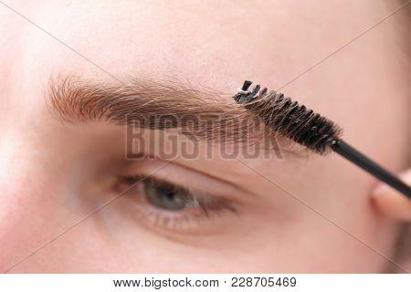 Artist correcting shape of man's eyebrow, closeup