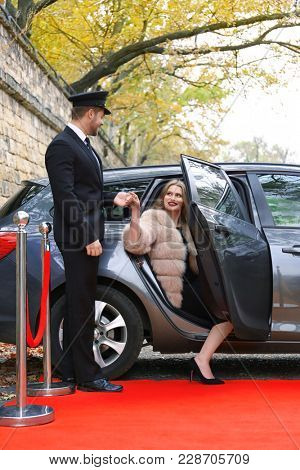Driver helping beautiful young woman to get out from car on red carpet