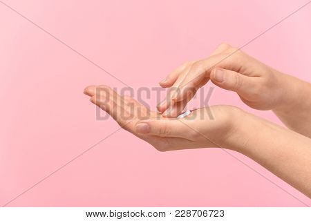 Woman applying body cream onto skin on color background