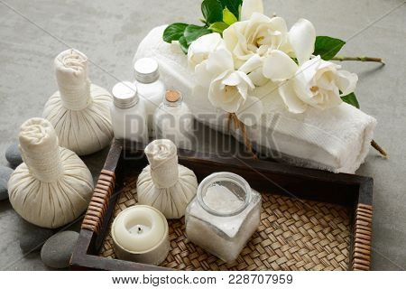 herbal ball, ,candle ,salt in glass in basket ,stones, towel, gardenia on gray background