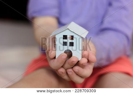 Small Kid Hands Holding White House Building