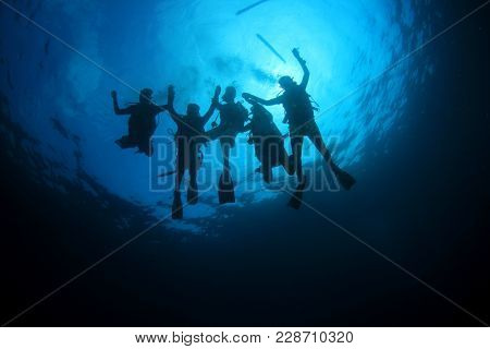 Scuba diving - group of divers silhouette underwater
