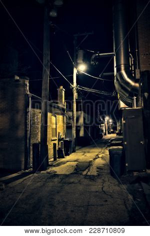 Dark empty scary urban city street alley and vintage industrial buildings at night
