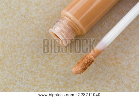 Doe-foot applicator next to tube of creamy concealer, high cover to conceal spots, blemishes, on yellow tile background