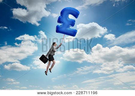 Businesswoman flying on british pound sign inflatable balloon