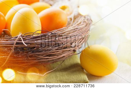Easter colorful eggs in the nest. Beautiful colorful yellow and orange color eggs with decorations on white wooden table background.
