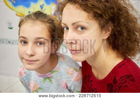 Mother and daughter with earrings in ears.