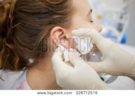 Doctor sterilize piercing place on ear of teenade girl.