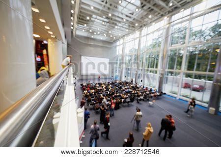 People listen to speaker in spacious auditorium, blurred image.
