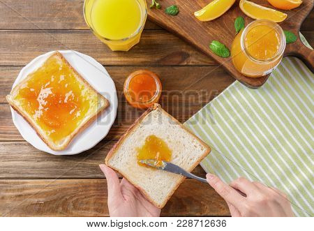 Woman spreading sweet jam on toast over table