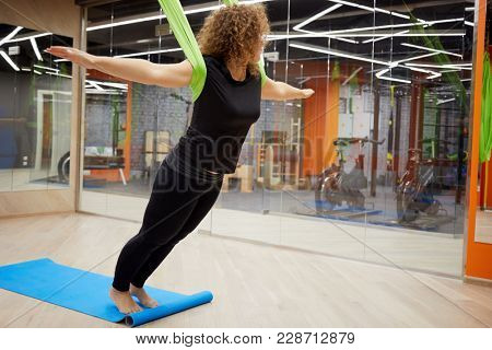 Woman doing exercise in gym with hammock for air flying yoga.