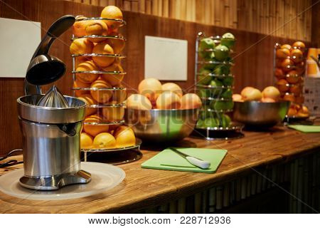 Bar counter with electrical juicer, spiral holders and bowls with oranges and apples, focus on juicer.