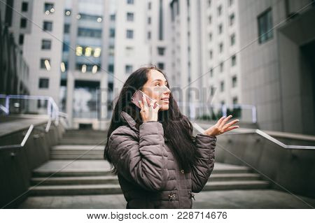 Young Girl Talking On Mobile Phone In Courtyard Business Center. Girl With Long Dark Hair Dressed In
