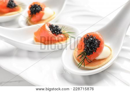 Tasty appetizers with black caviar and salmon in ceramic spoons on plate