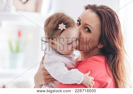 Young mother kissing her baby daughter. Family love concept. Motherhood.
