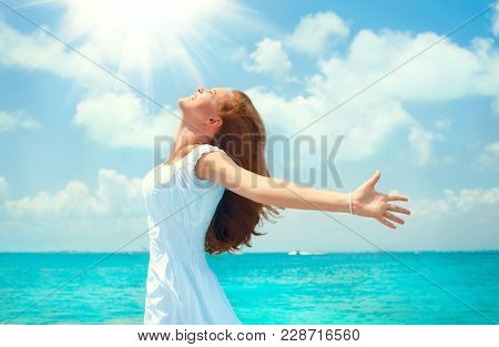 Travel or Vacation Concept. Beautiful Girl on the Ocean Beach raising hands, enjoying nature and smiling. Beautiful happy young woman in white dress on tropical resort island. Free, freedom