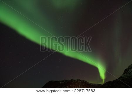 Bright Green Northern Light (aurora Borealis) Lighting Up The Dark Skies Above The Mountains, Tromsø