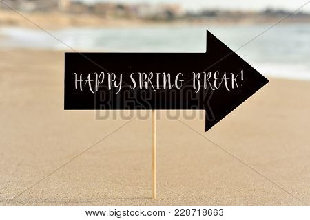an arrow-shaped signboard with the happy spring break written in it, on the sand of a quiet beach, and the sea in the background