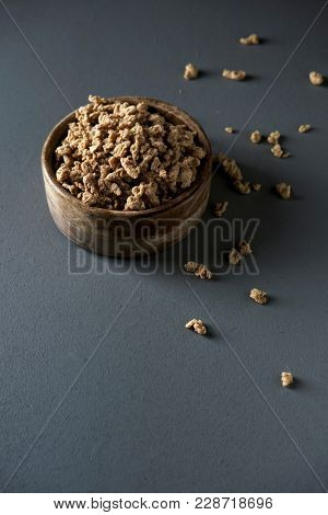 some chunks of textured soy protein in a rustic wooden bowl, on a gray wooden table with some blank space