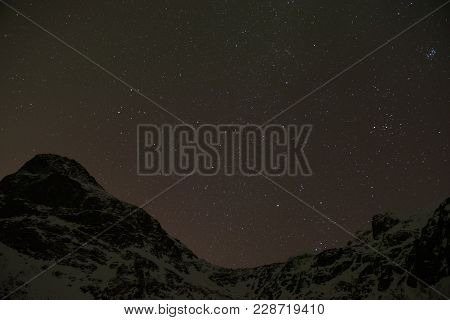 Clear Sky During A Starry Night Above The Mountains Surrounding A Norwegian Fjord Near Tromso