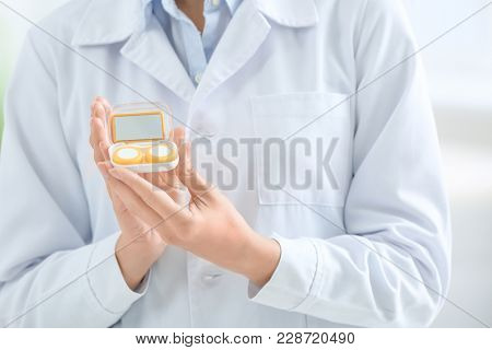 Female doctor holding contact lens case, closeup