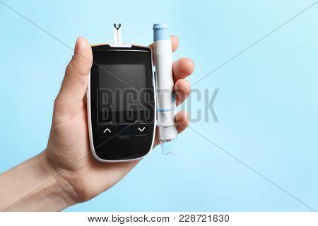 Woman holding digital glucometer and lancet pen on color background. Diabetes concept