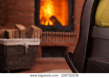 Detail of fireplace and rocking chair - cozy place at home for relaxing