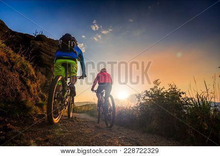 Mountain biking women and man riding on bikes at sunset mountains forest landscape. Couple cycling MTB enduro flow trail track. Outdoor sport activity.