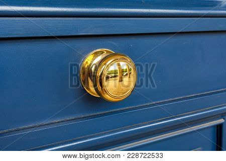 Rounded yellow handle on wooden door in Paris, France.