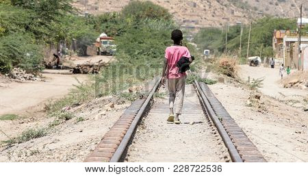 Child walking down railroad track in the desert of Ethiopia near Somalia.