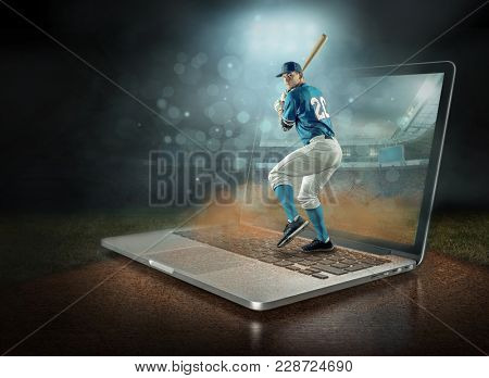 Caucassian baseball Player in dynamic action in a professional sport game play on the laptop in baseball under stadium lights.