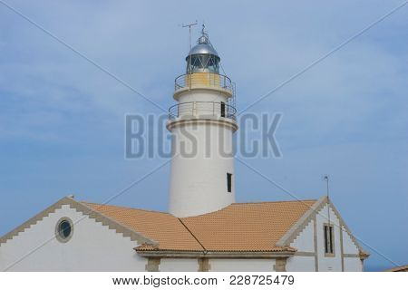Navigation, lighthouse next to the Mediterranean Sea, blue sky without clouds with calm waters. serves to warn ships of the presence of rocks