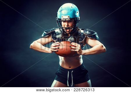 Sportive Serious Woman In Helmet Of Rugby Player Holding Ball And Screaming Aggressively.