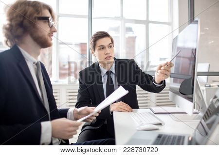 Elegant analyst or sales manager pointing at computer monitor while explaining online data to business partner