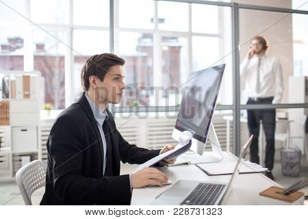 Young analyst in suit sitting by desk in front of computer monitor, reading document and comparing its information with that in the net