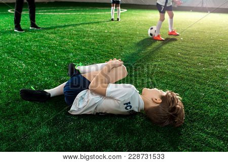 Hitted football player lying on the field and holding by hurt knee after accident
