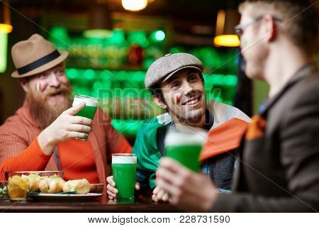 Smiling man with glass of beer listening to one of companions during talk while sitting in bar