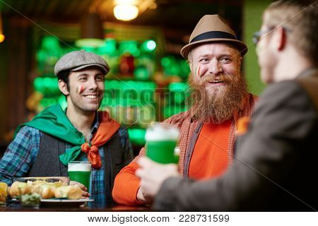 Bearded man and his young companion having talk to their friend by glass of beer in bar
