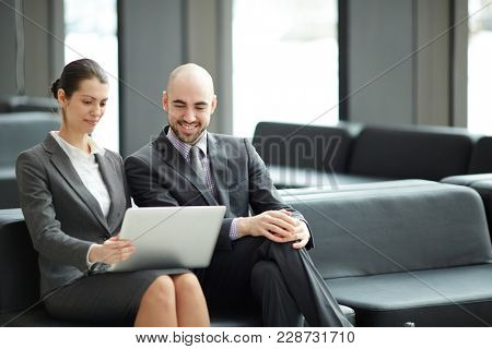 Two young successful business partners or analysts with laptop sitting on black leather sofa in airport lounge and looking through online statistics
