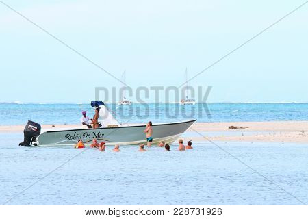 ILE AUX CERFS ISLAND/ MAURITIUS - FEBRUARY 25, 2018: Group of tourists enjoying life on white beach in famous tropical resort near Mauritius coast.