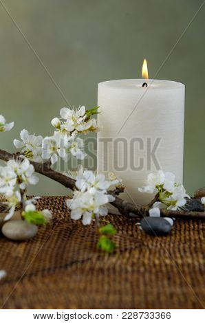 Spa resort with white candle, ,lying on cherry flower,stones